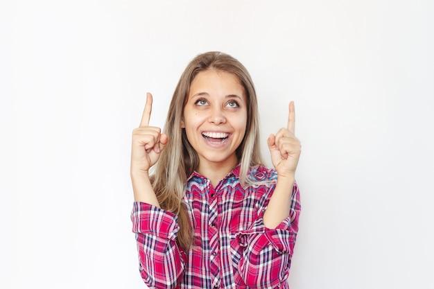 Una mujer joven señala un espacio en blanco vacío de copia para texto o diseño con dos dedos