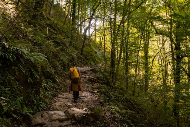 Una mujer joven en el sendero que se dirige a passerelle de holtzarte de larrau en el bosque o selva de irati, al norte de navarra en españa y los pirineos atlánticos de francia