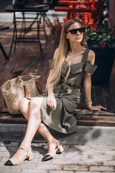 Mujer joven sentada afuera del café