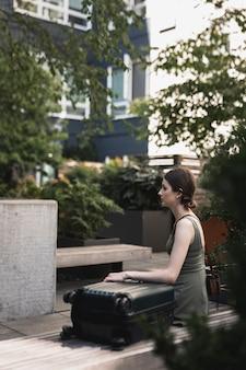 Mujer joven sentada en el asiento de cemento