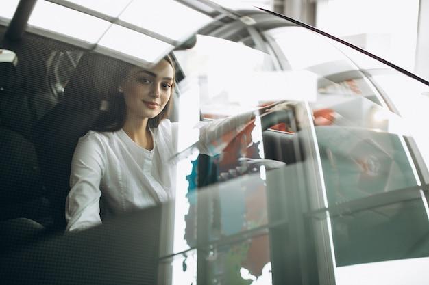 Mujer joven sentada en un automóvil en una sala de exposición de automóviles