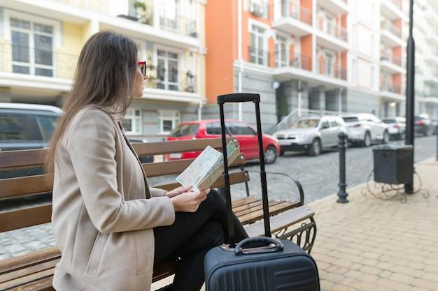 Mujer joven sentada en un banco con mapa, maleta