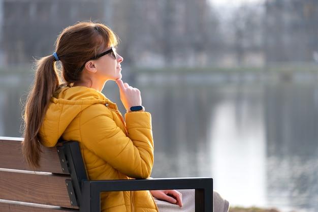 Mujer joven sentada en un banco del parque relajante en un cálido día de primavera.