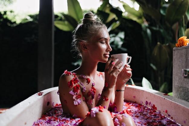 Mujer joven sentada en el baño con los ojos cerrados y bebiendo té caliente. retrato de niña magnífica con cabello rubio haciendo spa y disfrutando de un café.