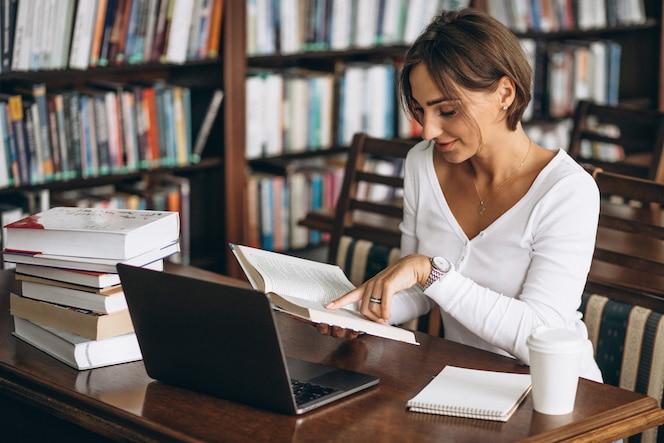 Mujer joven sentada en la biblioteca con libros y computadora