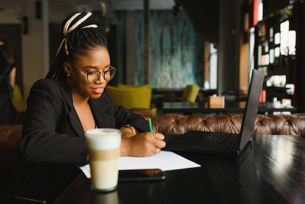 Mujer joven sentada en un café escribiendo en papel
