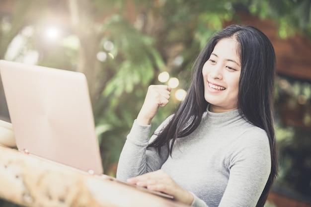 Mujer joven sentada en la cafetería en la mesa de madera, tomando café y usando la computadora portátil.