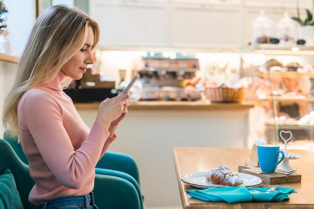 Mujer joven sentada en la cafetería con teléfono móvil