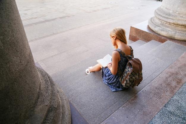 Mujer joven sentada en la calle usando una tableta
