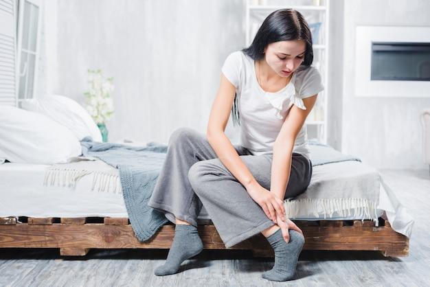 Una mujer joven sentada en la cama con dolor en el tobillo