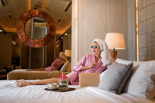 Mujer joven sentada en la cama en el interior del dormitorio moderno con su portátil y trabajando. diseño moderno para dormitorio. relajación después de los días de trabajo.