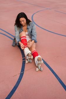 Mujer joven sentada en la cancha de fútbol atando un cordón de patín