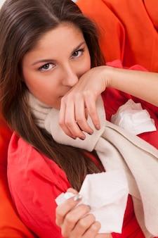 Mujer joven sentada en casa con frío