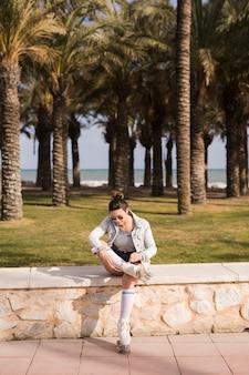 Mujer joven sentada cerca del banco que ata el cordón del patín