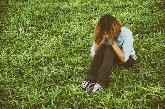 Mujer joven sentada en el césped llorando
