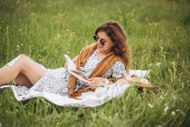 Mujer joven sentada en el césped en el parque y libro resing