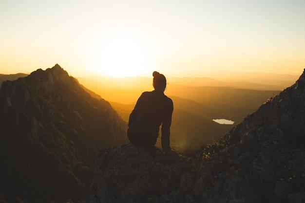 Mujer joven sentada en la cima de la montaña y disfrutando de la vista durante la puesta de sol