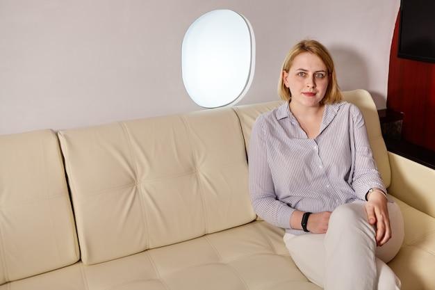 La mujer joven está sentada en la clase ejecutiva del avión cerca del ojo de buey.