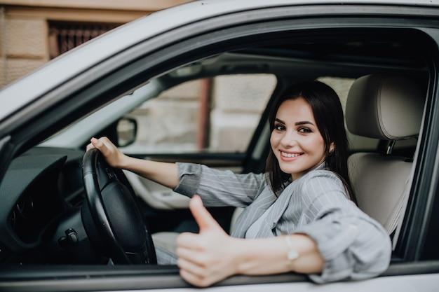 Mujer joven sentada en el coche y mostrando los pulgares para arriba