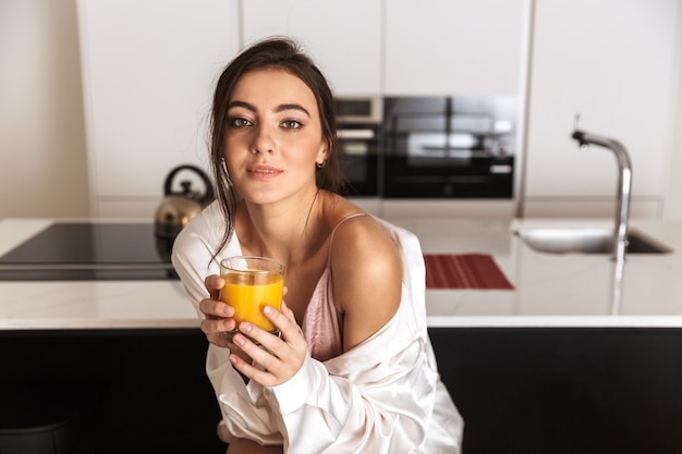 Mujer joven sentada en la cocina, sosteniendo un vaso con jugo de naranja