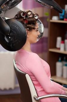 Mujer joven sentada debajo del secador de pelo con rodillos