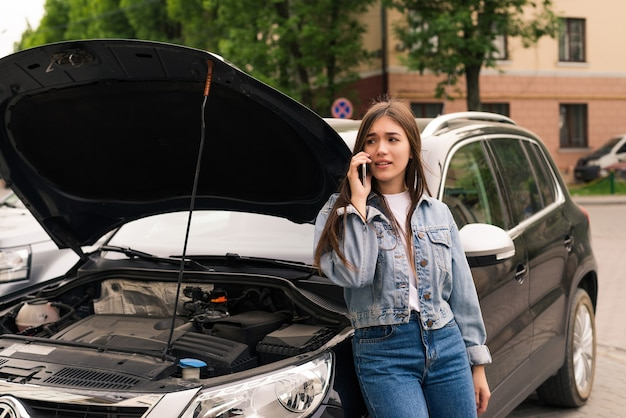 Mujer joven sentada delante de su coche, intenta pedir ayuda con su coche averiado
