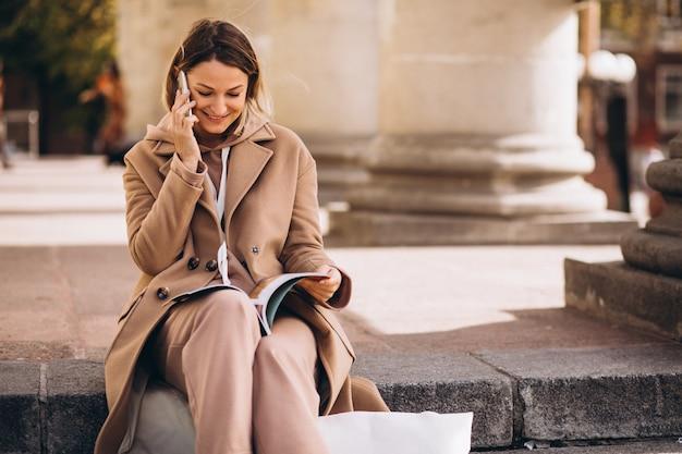 Mujer joven sentada en las escaleras de la ciudad y leyendo revistas y hablando por teléfono