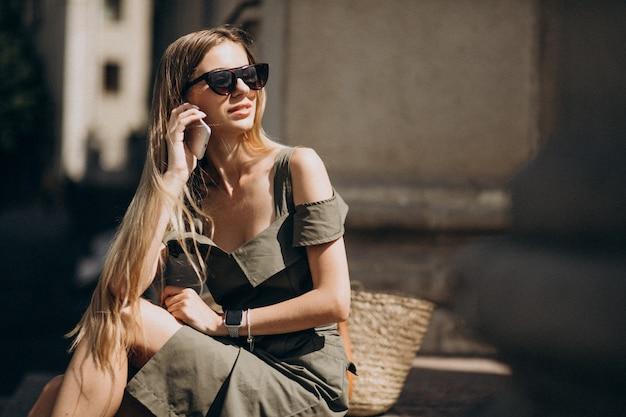 Mujer joven sentada en las escaleras y hablando por teléfono