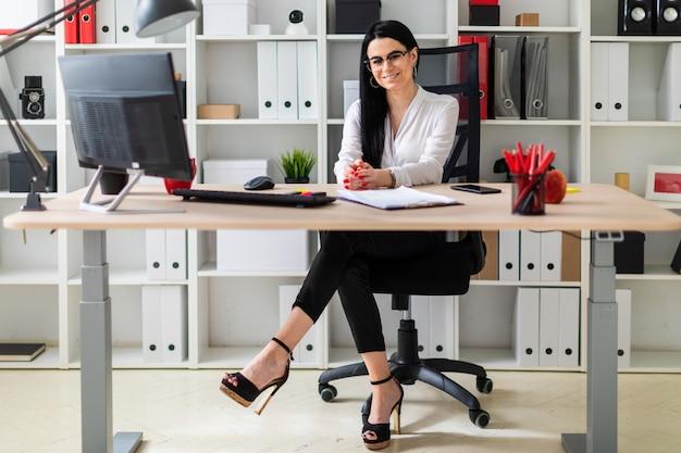 Una mujer joven está sentada en el escritorio de la computadora. al lado de la mujer se encuentran documentos y un marcador.