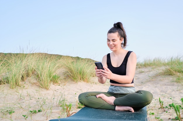 Mujer joven sentada en una estera mirando su teléfono inteligente durante una sesión de formación