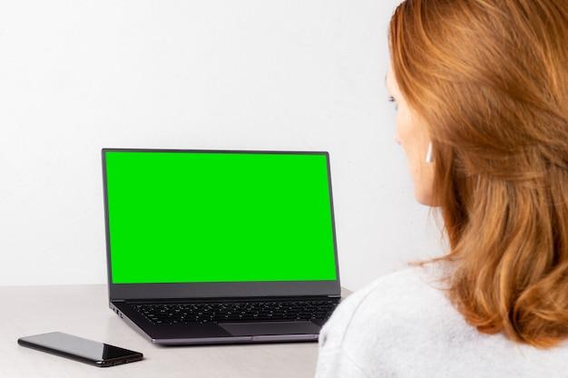 Mujer joven sentada frente a una computadora portátil con una maqueta verde en la pantalla