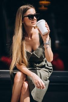 Mujer joven sentada fuera de la cafetería tomando café