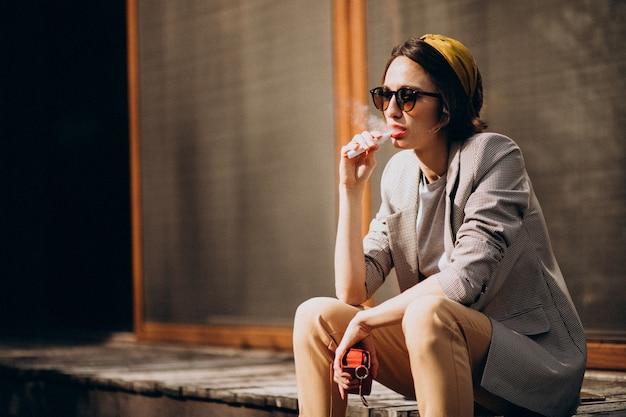 Mujer joven sentada y fumando ecigarette