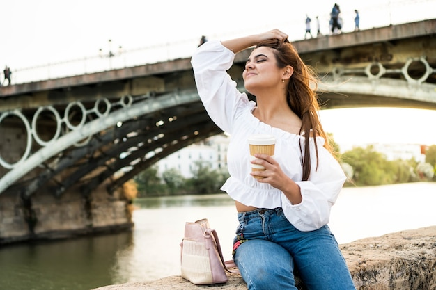 Mujer joven sentada junto al río chica con un café en sevilla españa turista en vacaciones de verano