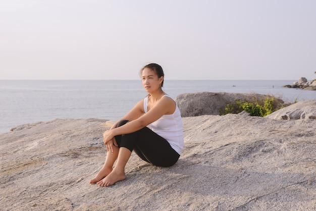 Mujer joven sentada en el mar al amanecer