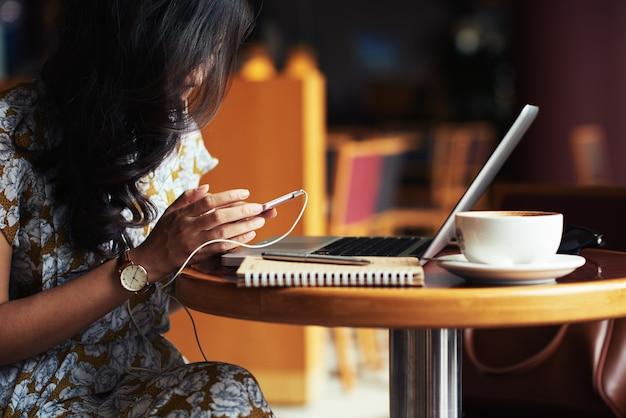 Mujer joven sentada en la mesa de café con ordenador portátil y teléfono inteligente