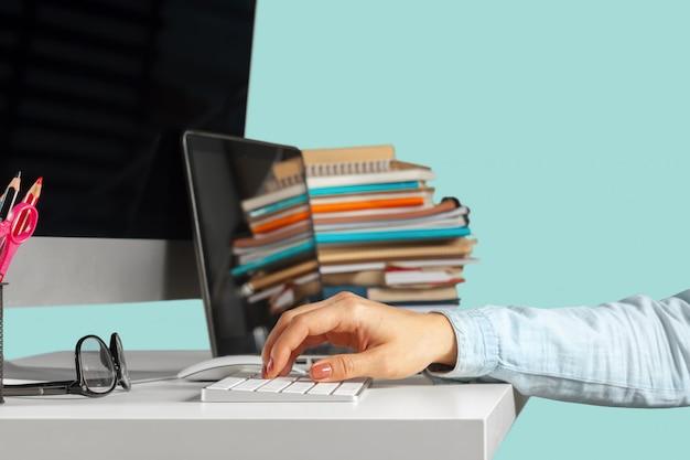 Mujer joven sentada en la mesa con la computadora netbook abierta