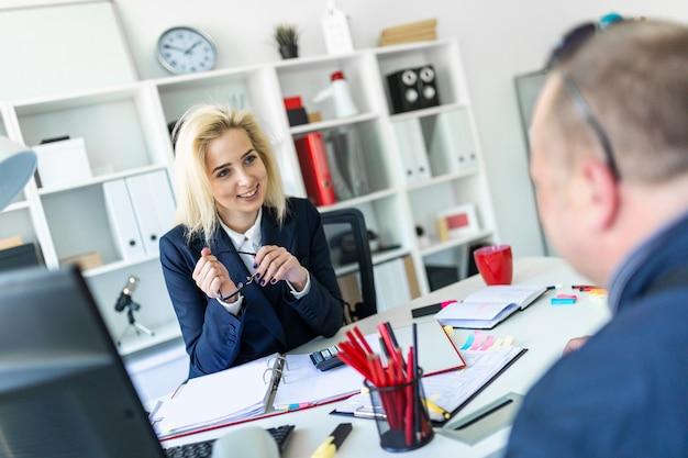 Una mujer joven está sentada en una mesa en la oficina, con gafas en la mano y hablando con un hombre.