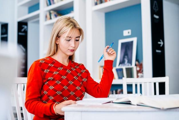 Mujer joven sentada en la mesa con pluma
