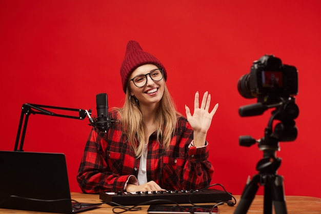 Mujer joven sentada en la mesa que trabaja como dj de radio ella sonriendo y saludando a la cámara en el estudio