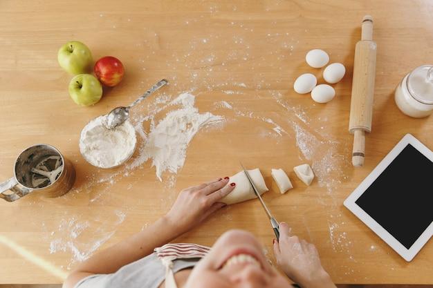 Una mujer joven sentada en una mesa con tableta, corta una masa con un cuchillo en pedazos en su casa en la cocina. cocinar en casa. prepara comida. vista superior.