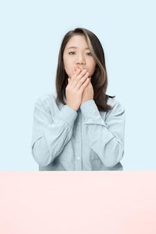 Mujer joven sentada a la mesa tapándose la boca aislada en azul.
