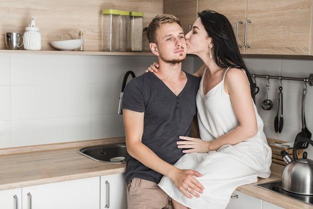 Mujer joven sentada en el mostrador de la cocina amando a su marido en sus mejillas