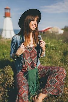 Mujer joven sentada en la naturaleza, faro, traje bohemio, chaqueta vaquera, sombrero negro, sonriente, feliz, verano, accesorios elegantes