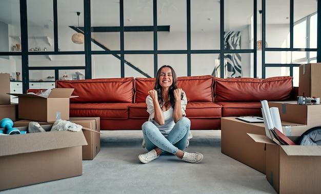 Mujer joven sentada en un nuevo apartamento y levantando los brazos de alegría después de mudarse. mudarse, comprar una casa, concepto de apartamento.