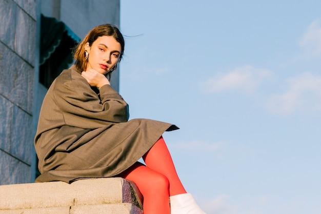 Mujer joven sentada en la pared con sus piernas cruzadas contra el cielo azul