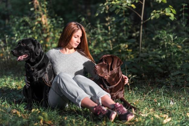Mujer joven sentada en el parque con sus dos labradores