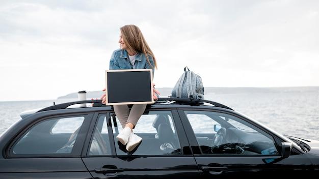 Mujer joven sentada en la parte superior del coche