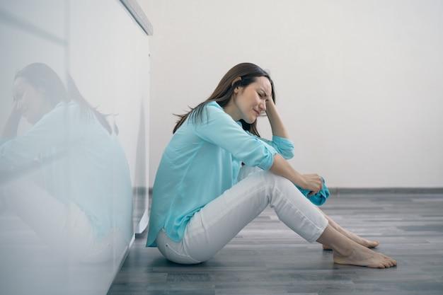 Mujer joven sentada en el piso de la cocina sosteniendo su cabeza y llorando, molesta, triste, deprimida