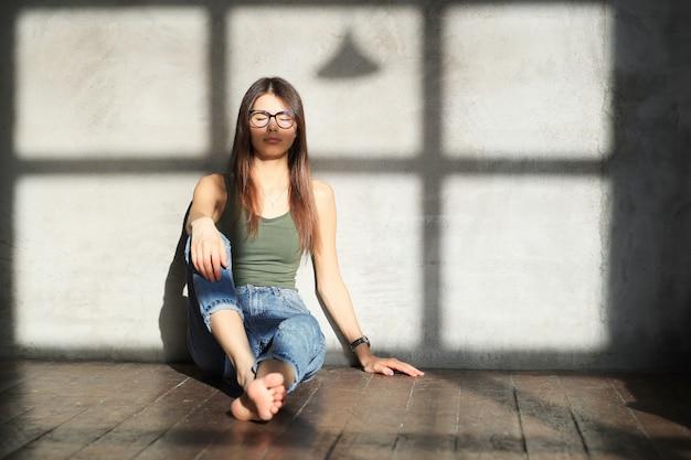 Mujer joven sentada en el piso de una habitación vacía
